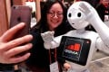 A visitor to the Mobile World Congress in Barcelona, Spain, takes a selfie with a robot from SoftBank Robotics, on February 28. Photo: Reuters