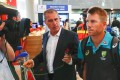 Australian cricket player David Warner (right) departs from Cape Town International airport after stepping down as vice captain. Photo: EPA