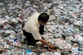 A City Hall worker spreads million of the pirated video compact disc (VCDs), software and CDs on the floor before destroying them in Kuala Lumpur. Photo: AP/Teh Eng Koon