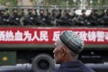 A Uygur man looks on as a truck carrying paramilitary police officers travels along a street in Urumqi, capital of China's far western Xinjiang region in this file image. Photo: Reuters