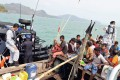 Malaysian navy officers detain a boat which carried Rohingya migrants off Langkawi, Malaysia. Photo: AP