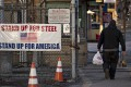 A man walks past a 'Stand Up For Steel, Stand Up For America' sign while arriving at the United States Steel Corporation Clairton Plant in Clairton, Pennsylvania, on March 11. US manufacturing has suffered after US President Donald Trump announced tariffs on foreign steel and aluminium, as prices shot up and companies panic-bought stocks. Photo: Bloomberg