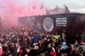 Liverpool supporters ignite red flares as the Manchester City team bus arrives to a heated reception at the gates of Anfield. Photo: EPA