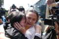 Liu Chengying (left) embraces her daughter Kang Ying during their reunion in Chengdu, as the press watch on. Photo: Xinhua