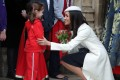 Meghan Markle, fiancée of Britain's Prince Harry receives a posy of flowers from a young girl after attending a Commonwealth Day Service at Westminster Abbey in central London. Photo: AFP