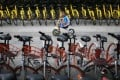 At one time, there were about 100 companies offering short-term bicycle rental services in China. A child rides past other bicycles from bike-sharing companies parked along a pavement in Beijing. Photo: AP