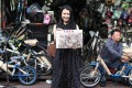 Illustrator Or Wai-wai displays a drawing of Wing Hing Bicycle outside the shop in Yau Ma Tei. Photo: Nora Tam