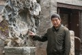 Former Red Guard Wu Jianguo with an old decorative stone, part of his collection of Chinese antiques and historical objects in rural Shaanxi province. Photo: Mark Andrews