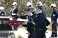 Japanese police inspect cars in Onomichi as they search for a jail breaker. Photo: AP