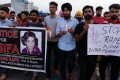 Indian students hold a banner with a photo of Asifa Bano, posters and candles during a march to protest against the rape and murder of eight-year-old Asifa Bano, in Amritsar, India. Photo: EPA