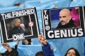 Manchester City fans hold up placards showing the faces of manager Pep Guardiola and Manchester United's Jose Mourinho during the derby. Photo: AFP
