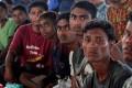 Ethnic Rohingya men gather inside a shelter. Photo: EPA