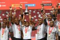 Fiji players celebrate with the trophy after defeating Australia in the Cup final of the Singapore Rugby Sevens tournament. Photo: AFP