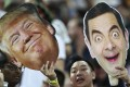 """A fan holds up cutouts of US President Donald Trump and Mr Bean, played by British actor Rowan Atkinson, during the HSBC World Rugby Sevens Series 2018 finals on April 29 in Singapore. Trump's """"madman"""" diplomacy might just secure him enough foreign policy wins to shore up his reputation at home. Photo: AP"""
