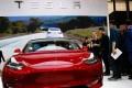 Visitors look at Tesla Model 3 car during Auto China 2018 motor show in Beijing, China, 25 April 2018. Photo: EPA-EFE
