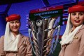 Two Emirates Airlines air hostesses pose next to the AFC Asian Cup trophy during the draw in Dubai. Photos: AFP