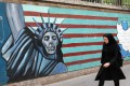 A woman walks past a mural on the wall of the former US embassy in the Iranian capital Tehran on Tuesday. Photo: AFP