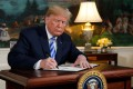 US President Donald Trump signing a proclamation declaring his intention to withdraw from the JCPOA Iran nuclear agreement in the Diplomatic Room at the White House in Washington on Tuesday. Photo: Reuters