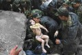 Soldiers rescue a child from the rubble after the magnitude-8 earthquake in Beichuan, Sichuan province May 13, 2008. Photo: Reuters