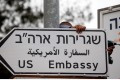 A worker hangs a road sign to the US embassy in Jerusalem. Photo: Reuters