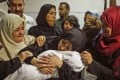 The mother of a Leila al-Ghandour, the Palestinian baby who according to the Palestinian health ministry died during clashes in East Gaza the previous day, holds her at the morgue of al-Shifa hospital in Gaza City. Photo: AFP