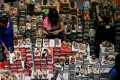 People shop for shoes at a mall in Singapore in May 2016. Online shopping has gained in popularity, but not brought down prices for every customer. Photo: Reuters