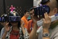 Participants at the China Hi-Tech Fair 2017, held in November in Shenzhen, try out the Qiyu virtual reality headset from iQiyi, a Netflix-style online video-streaming company controlled by Baidu. Photo: Handout