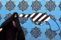 An Iranian woman walks past a mural on the wall of the former US embassy in the Iranian capital Tehran on May 8. Photo: Agence France-Presse
