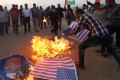 Palestinian demonstrators burn representations of US flags and a poster of US President Donald Trump during a protest marking the 70th anniversary of Nakba and against the US embassy move to Jerusalem, at the Israel-Gaza border in the southern Gaza Strip on Tuesday. Photo: Reuters