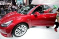 A man cleans a Tesla Model 3 car during a media preview at the Auto China 2018 motor show in Beijing last month. In a series of tweets over the weekend, Tesla chief executive Elon Musk unveiled specifications for a faster and more powerful version of the Model 3. Photo: Reuters