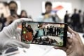 An attendee tests the augmented reality function of the Xiaomi Corp. Mi MIX 2S smartphone at an unveiling event in Shanghai, China, March 27, 2018. Photo: Bloomberg.