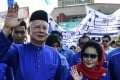 Najib Razak and his wife Rosmah Mansor waving as they arrive at a nomination centre to hand over election documents in Pekan, Malaysia. Photo: AFP