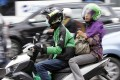 A woman rides on the back of a motorbike, part of the Go-Jek ride-hailing service, on a busy street in central Jakarta, Indonesia. Photo: Reuters