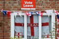 English Cross of St George flags hang in a windows with a Vote Leave poster in Redcar, northeast England on June 27, 2016. Photo: Agence France-Presse