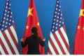 A Chinese woman adjusts a Chinese flag near US flags before a meeting between the countries in Beijing in 2014. Photo: AFP