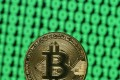 A token of the virtual currency Bitcoin is seen placed on a monitor that displays binary digits. Photo: Reuters