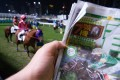 A punter checks the horse form at Happy Valley racecourse, in Hong Kong. Picture: Alamy