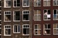 A resident looks out from the window of a residential property in Amsterdam. Housing prices in the capital city have soared. Photo: Bloomberg