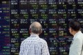 Investors watch a share prices board in Tokyo. Photo: AFP PHOTO