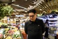 Kim Jong-un impersonator Howard X in a supermarket in Hong Kong. Photo: Anthony Wallace