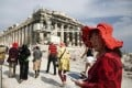 A Chinese tourist carries a tablet device during a visit to the Parthenon at the Acropolis archaeological site in Athens, Greece. Photo: Bloomberg