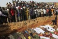 In this 2010 file photo, villagers look at bodies of victims of violence between ethnic Berom farmers on Fulani herders lying in a mass grave in the Dogo Nahawa village in central Nigeria. The ongoing violence is threatening to become the worst security risk in the country. Photo: Reuters