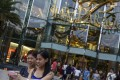 Tourists take a photo of themselves in front of Siam Paragon Department Store in central Bangkok. Photo: Reuters