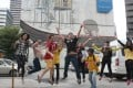 Tour participants jump in front of a mural after being shown around Kuala Lumput by a Yellow House KL guide. Photo: TK Letchumy