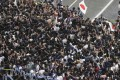 Police try to control Japanese soccer fans celebrating their victory over Colombia in the World Cup. Photo: Reuters