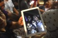 A family member shows the latest pictures of the missing boys taken by rescue divers inside Tham Luang cave when all members of the youth football team and their coach were found alive. Photo: AFP