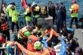 Thai rescuers carry tourists' bodies aboard a navy vessel after it sank, as search and rescue operations continue in the seas off Phuket island, southern Thailand, on Saturday. Photo: EPA-EFE