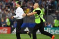 A member of Russian protest group Pussy Riot is grabbed by security after storming the pitch at the World Cup final between France and Croatia yesterday. Photo: AFP