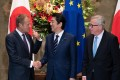 Donald Tusk, president of the European Council, left, shakes hands with Shinzo Abe, Japan's prime minister, while Jean-Claude Juncker, president of the European Commission, looks on. Photo: Bloomberg