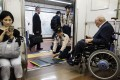 Subway employees help an elderly man in a wheelchair to disembark from the train at a station in Tokyo. Photo: AFP